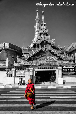 A red robed monk with the Sule Pagoda in the background