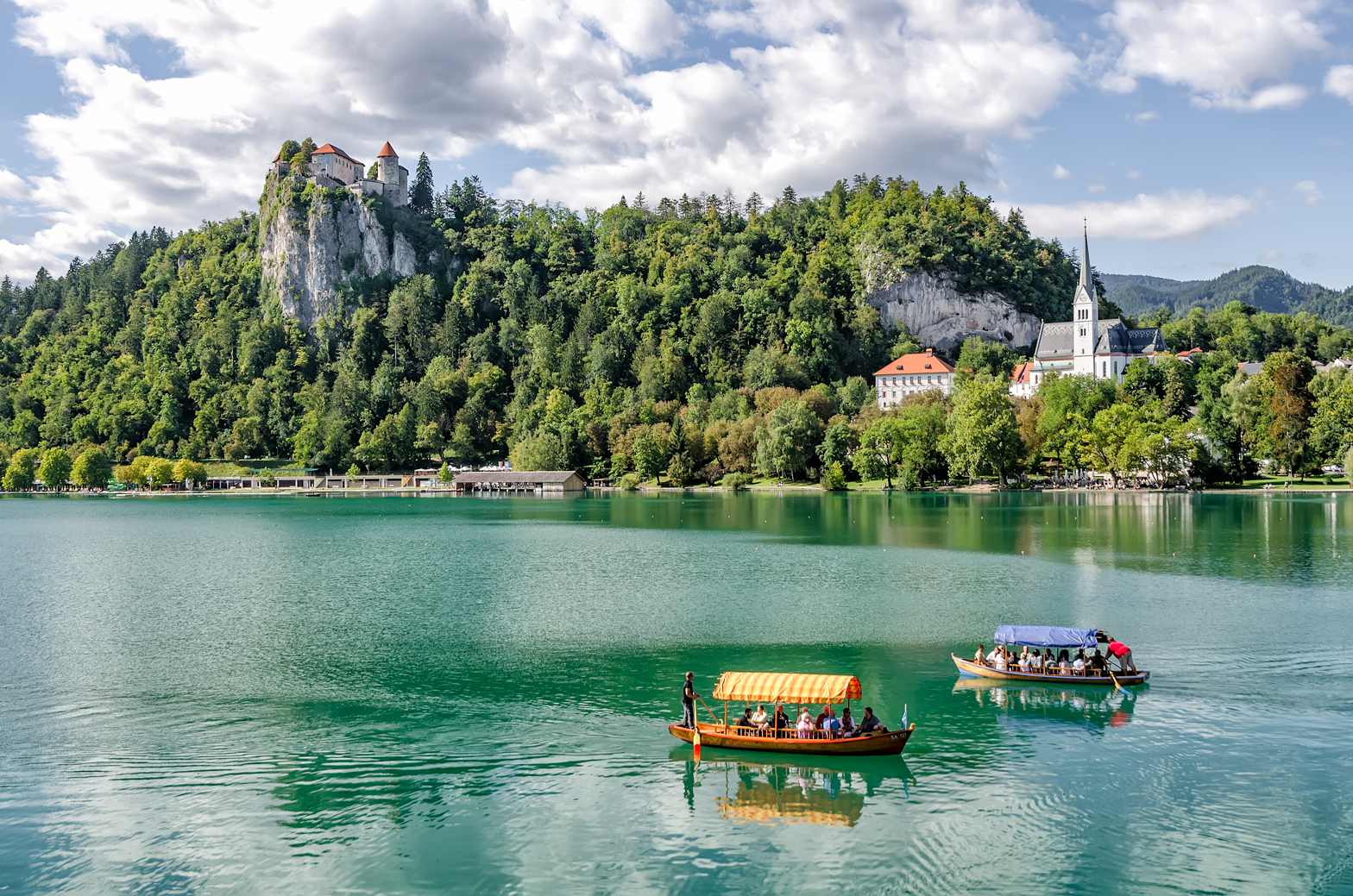 Lake Bled with Pletnas rowing across and Bled Castle keeping watch above