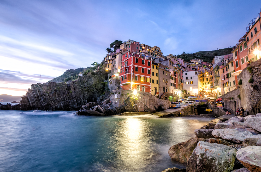 Twinkling lights come on in Riomaggiore at dusk